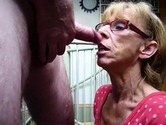 Slutty mature lady with glasses kneels down and blows a dick
