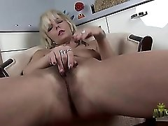Blonde with a bush opens her legs and masturbates