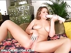 Curly haired babe fills her pink pussy with thick dildo